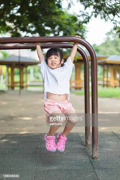 Little girl playing horizontal bar in park