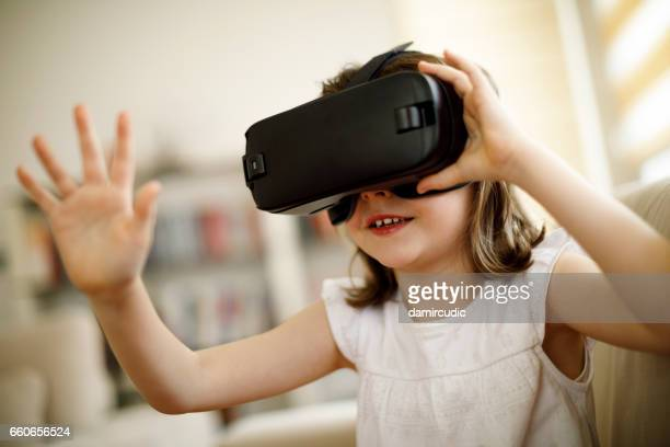 little girl playing imaginary game with virtual reality headset - human interest stock pictures, royalty-free photos & images