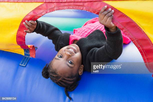 little girl playing in bounce house - preschool student stock pictures, royalty-free photos & images