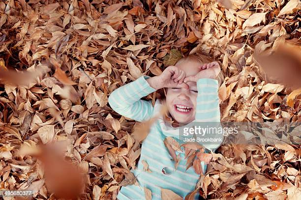 little girl playing in fall leaves - girl mound stock pictures, royalty-free photos & images