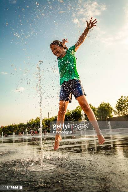 little girl playing in fountains at outdoor splash pad - fountain stock pictures, royalty-free photos & images