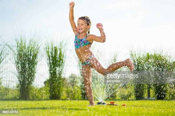 liten flicka som leker i trädgården kör över vatten sprinkler - värmebölja bildbanksfoton och bilder