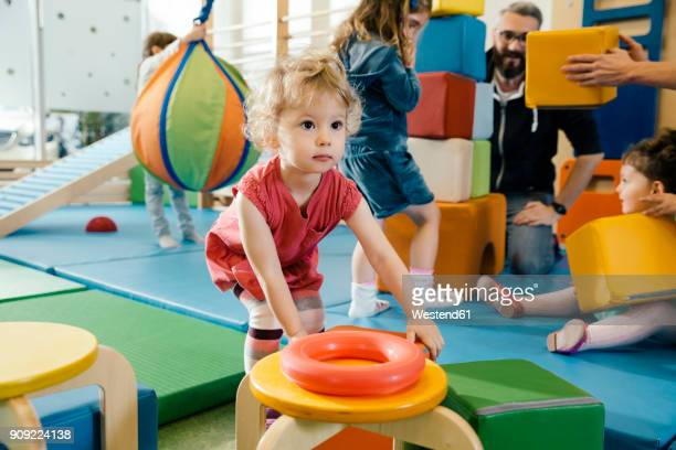 little girl playing in gym room of a kindergarten - kindergarten stock-fotos und bilder
