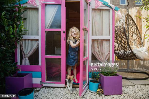 Little Girl Playing in Her Garden Playhouse
