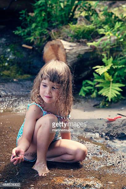 Little girl playing in lake water in summer nature.