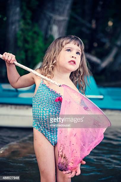 Kleines Mädchen spielt im See Wasser mit landing netto.