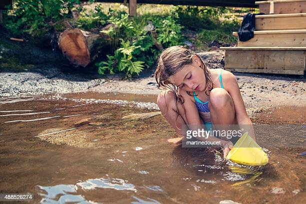 """little girl playing in lake water with yellow bucket. - """"martine doucet"""" or martinedoucet stock pictures, royalty-free photos & images"""
