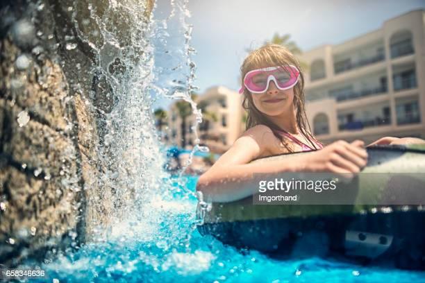 リゾート プールで遊ぶ少女。