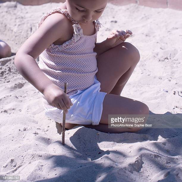 little girl playing in sand with stick - 2 girls 1 sandbox stock photos and pictures