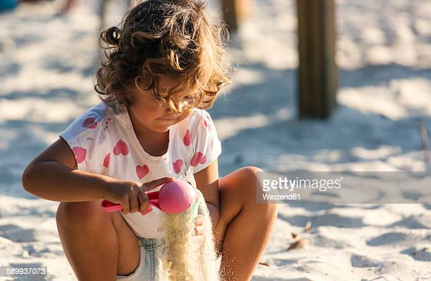 Little girl playing in sandbox on playground