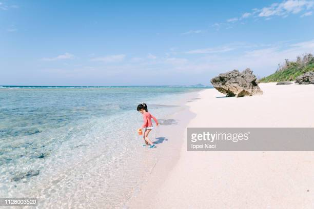 Little girl playing in shallow tropical water of white sand beach, Japan