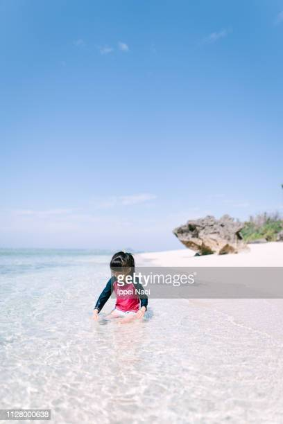 Little girl playing in shallow tropical water with white sand beach, Japan