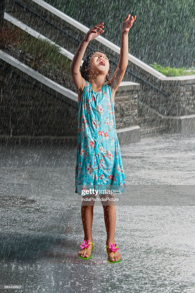 Little girl playing in the rain : Stock Photo