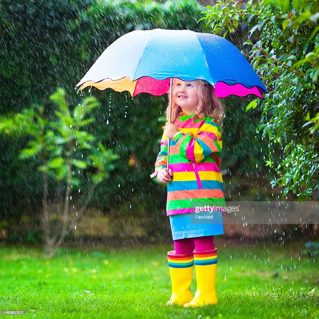 Little Girl Playing In The Rain Under Colorful Umbrella Stock Photo ...