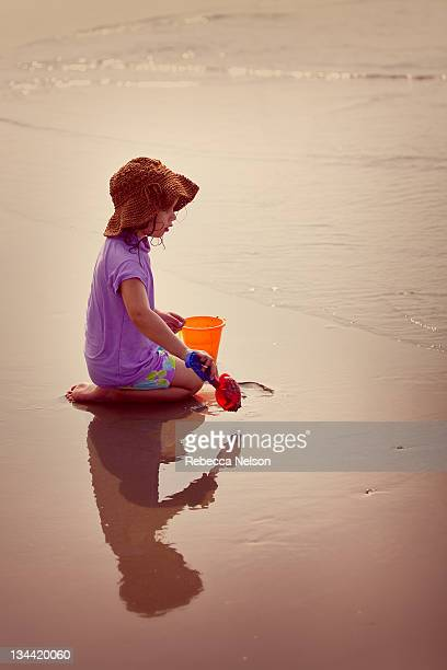 little girl playing in wet sand at seashore - rebecca nelson stock pictures, royalty-free photos & images