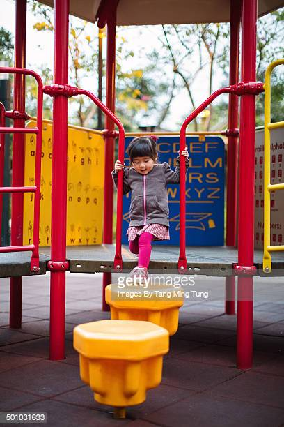 Little girl playing joyfully in playground