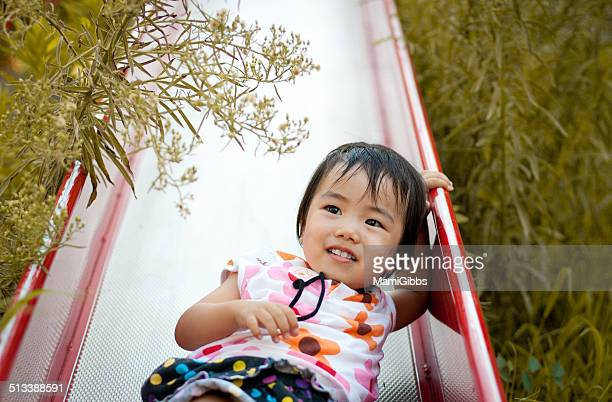 Little girl playing on a slide