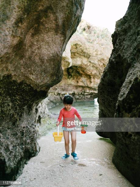 Little girl playing on beach in cave, Okinawa, Japan
