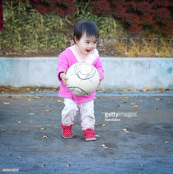Little girl playing on football