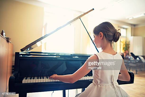 little girl playing on grand piano - grand piano stock photos and pictures