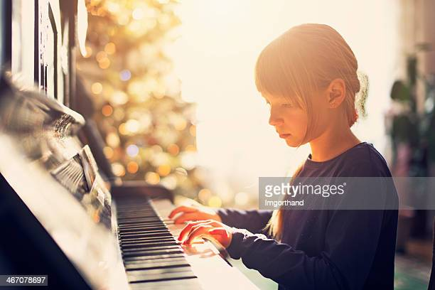 Little girl playing on grandmother piano