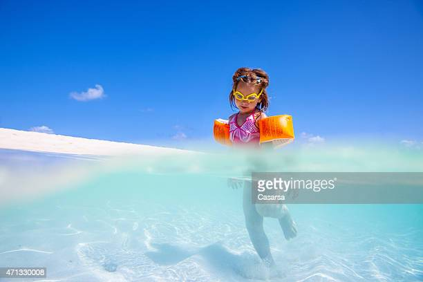 Little girl playing on idylic beach