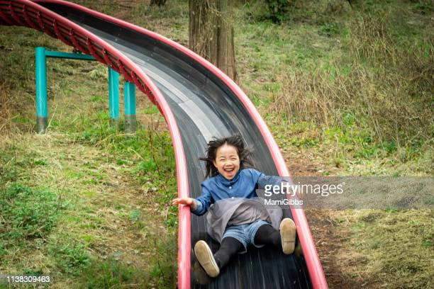 little girl playing on park - sliding stock pictures, royalty-free photos & images
