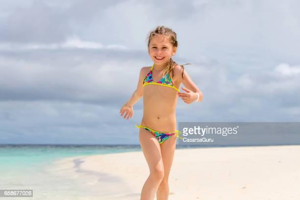 little girl playing on sandy beach - solo bambine femmine costume da bagno foto e immagini stock
