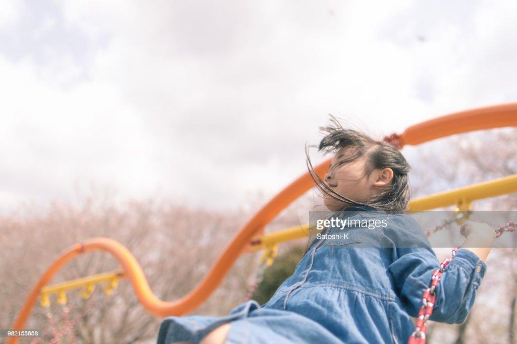 Little girl playing on swing : Stock Photo