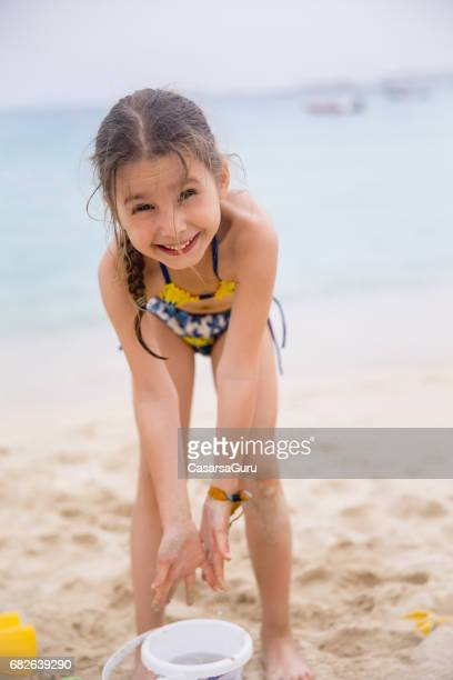 little girl playing on the dubai beach - little girls bent over stock photos and pictures