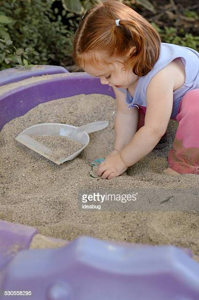 Little Girl Playing Outside in Sandbox