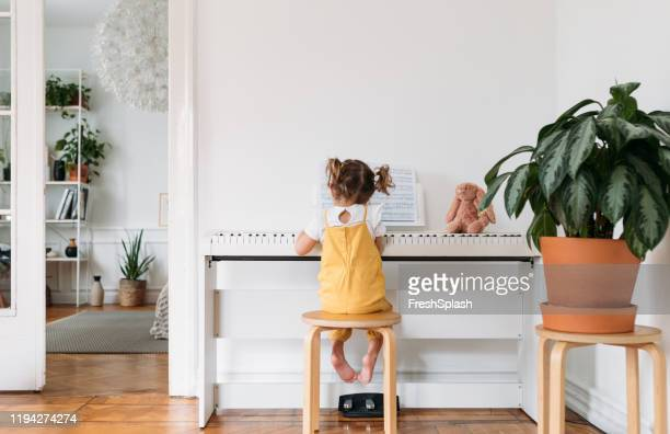 little girl playing piano - vertebrate stock pictures, royalty-free photos & images