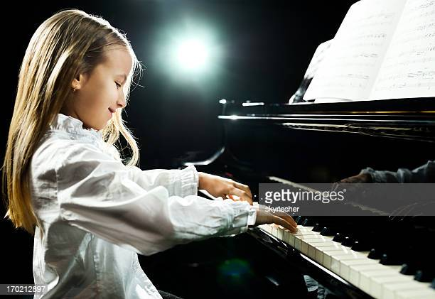 Little girl playing piano with sheet music
