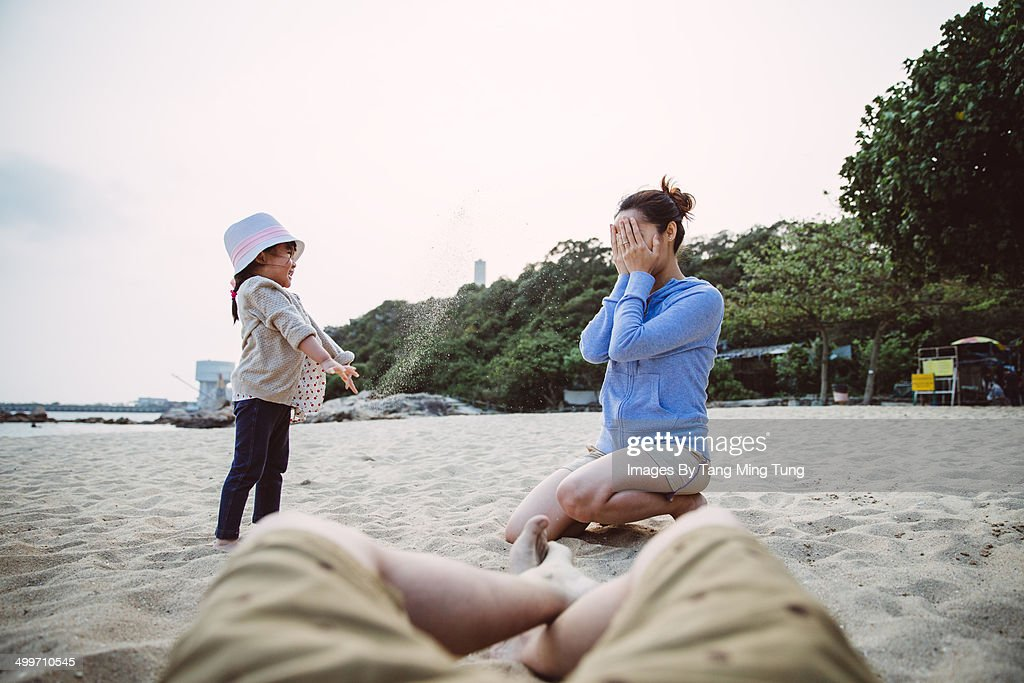 Little girl playing sand with mom on the beach : Stock Photo