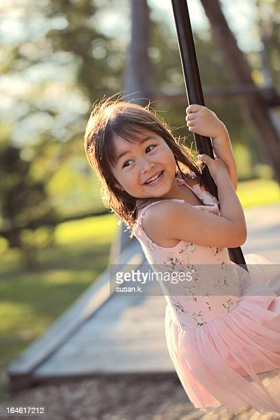 Little girl playing single rope swing joyously.