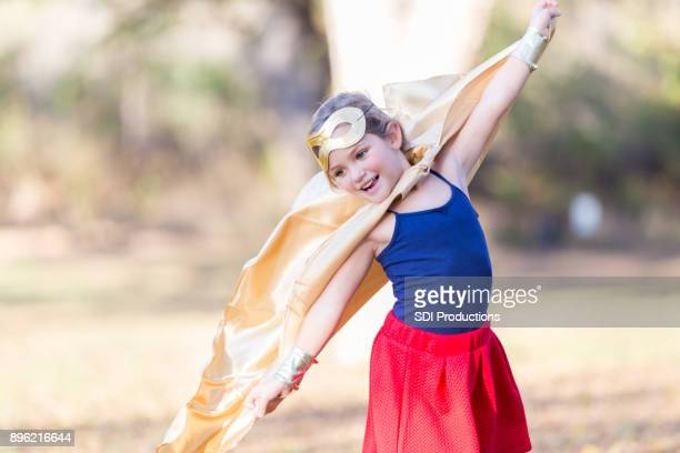 Little girl playing superhero in mid pretend flight