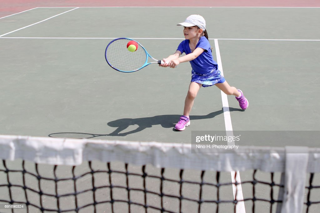 Little girl playing tennis : ストックフォト