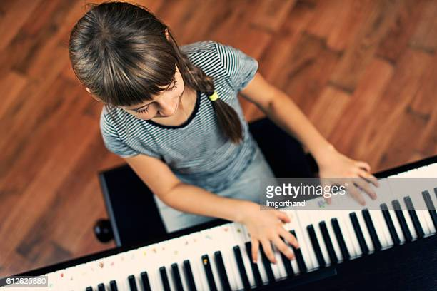 little girl playing the digital piano - electric piano stock photos and pictures
