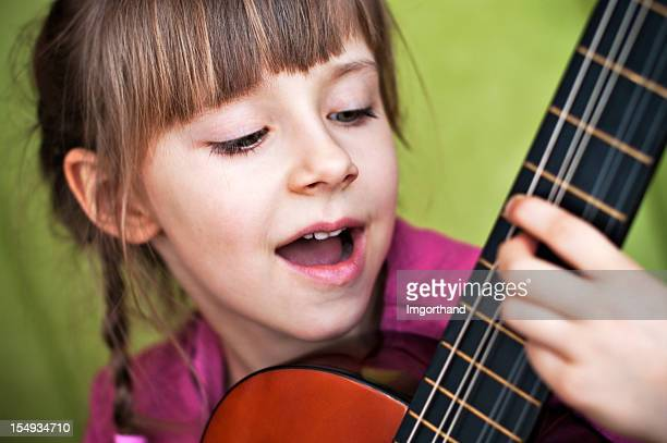 Kleines Mädchen spielt Gitarre und singt