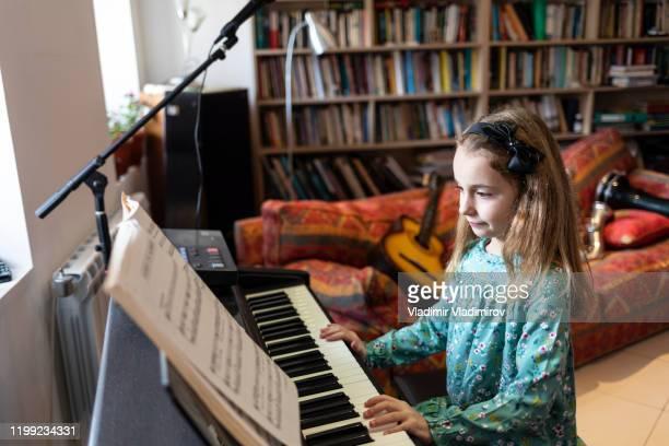 一人でピアノを弾いている小さな女の子 - キーボード奏者 ストックフォトと画像