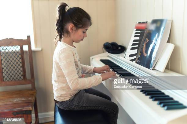 little girl playing the piano in living room at home, uk, quarantin covid-19, - キーボード奏者 ストックフォトと画像