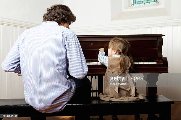 little girl playing the piano with father