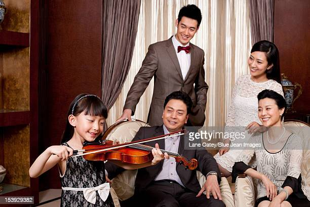 Little girl playing violin in front of family members