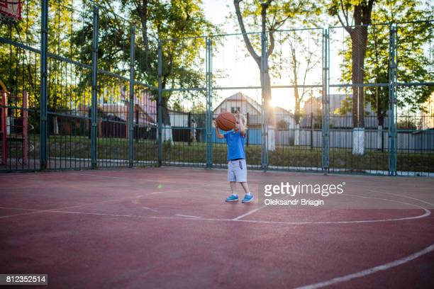 Little girl playing with a basketball in a court