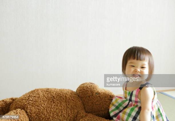 Little girl playing with a big teddy bear