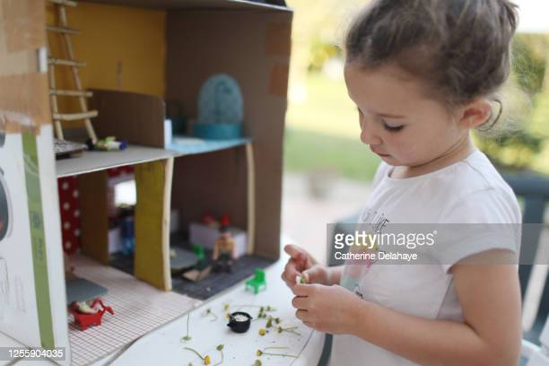 a little girl playing with a cardboard dollhouse - ドールハウス ストックフォトと画像