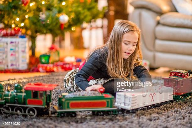 Little Girl Playing with a Christmas Train