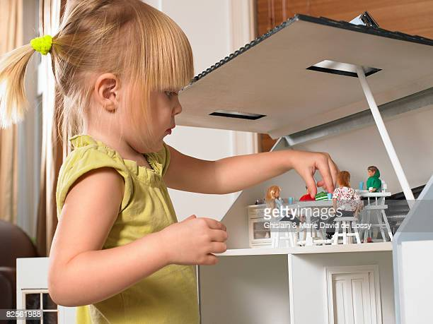 Little girl playing with a doll house