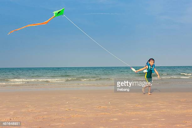 Little girl playing with a kite on the beach