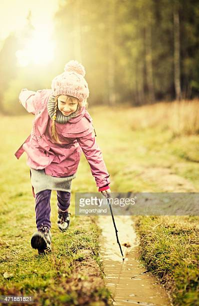 little girl playing with a puddle - imgorthand stock photos and pictures